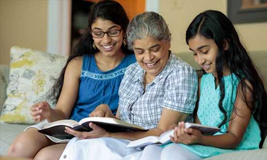 Woman and girls reading Bible - American Bible Society